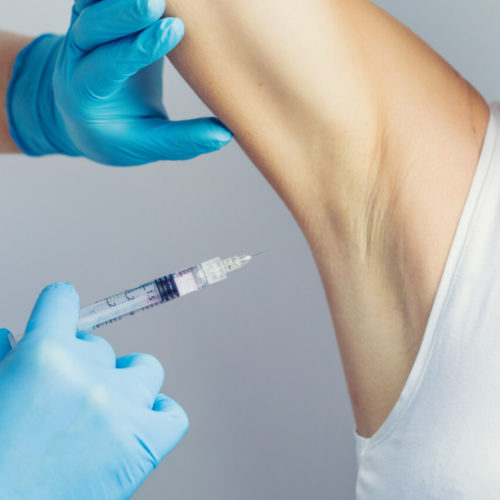 A person lifting their underarm whilst someone holds a needle
